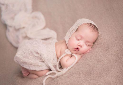newborn baby in lace bonnet