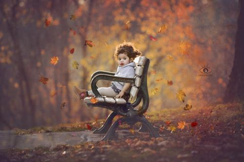 girl sitting on a bench with falling leaves