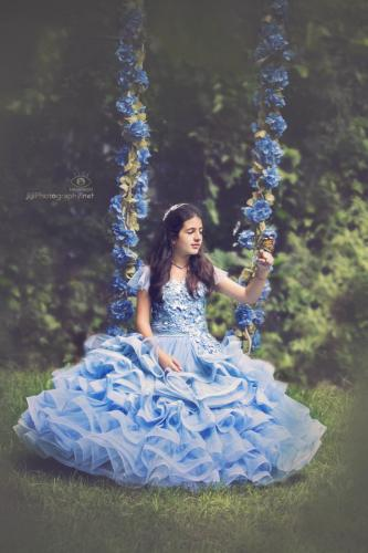 girl in a blue dress sitting on a magical swing
